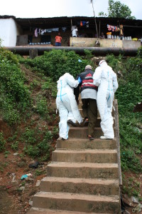 Handicap International staff helping man evacuated to an Ebola testing centre.
